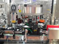 Sistema automatico sincronizzato per la rullatura o termoretrazione delle capsule.